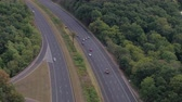 turnpike : AERIAL: Flying above busy multilane interstate expressway crowded with speeding vehicles. Personal cars commuting and traveling on holidays, semi trucks and trade trailers shipping loaded cargo by day
