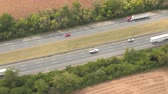 multilane : AERIAL: Personal cars driving on multilane interstate highway, commuting and traveling on holidays. Semi trucks and trade trailers shipping loaded cargo, traveling through rural landscape on sunny day Stock Footage