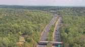 turnpike : AERIAL ESTABLISHING SHOT: Multiple lane highway leading towards New York City skyline on horizon. Semi trucks and cars driving along the busy interstate freeway past the green suburbs towards New York