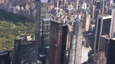 upper east side : AERIAL CLOSE UP: Sunny New York city midtown Manhattan with contemporary glassy skyscrapers and condominium apartment buildings overlooking beautiful green Central park. Busy crowded NYC in America Stock Footage