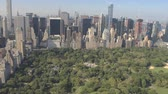 upper east side : AERIAL ESTABLISHING SHOT: Flying above Central Park along 5th Avenue and towards Downtown Manhattan in sunny New York City. Tall glassy skyscrapers and condominium buildings overlooking Central Park Stock Footage