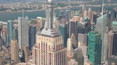 közép amerika : AERIAL CLOSE UP ZOOM LENS: Flying around iconic Empire State building in sunny New York city with midtown Manhattan, Hudson river and central park in the background. Helicopter flight above New York