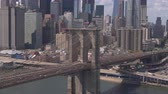 multilane : AERIAL: Beautiful cityscape of iconic downtown New York City skyscrapers, office buildings and financial district high-raise towers. Busy Brooklyn Bridge highway with cars and semi trucks on sunny day