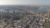 flat roof : AERIAL: Flying high above rooftops of NY City office buildings, tower blocks, residential apartments, condominiums and luxury hotels in Manhattan overlooking the two bridges and Brooklyn neighborhood Stock Footage