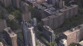 pendulares : AERIAL: Highly populated condominium residential buildings and local avenue streets crowded with personal cars and yellow taxicabs driving in Manhattan neighborhood in iconic New York City, America