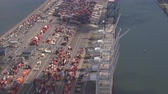 грузоперевозки : AERIAL: Colorful containers in large maritime trade and transportation freight harbor in sea port of New York City. Semi trucks unloading heavy cargo shipments for import and export via ship transport