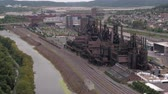 smelting : AERIAL: Flying above antique steelstacks iron works strategically placed near river current and railway road in small industrial American town in valley surrounded with overgrown lush green mountains Stock Footage