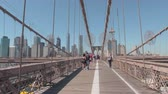 puente de manhattan : NEW YORK, USA - SEPTEMBER 23rd 2016: Smiling tourists crossing famous Brooklyn Bridge sightseeing and taking pictures on beautiful sunny day on trip to Lower Manhattan downtown in iconic New York City