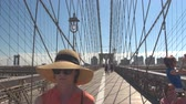 borough : NEW YORK, USA - SEPTEMBER 23rd 2016: Cheerful tourists crossing famous Brooklyn Bridge and taking photos on their way to NYC downtown. Iconic bridge on sunny summer day overlooking Brooklyn borough