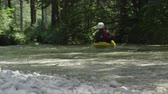 szlovénia : DOF: Extreme pro canoer paddling down the rocky river stream around natural obstacles in riverbed and enjoying beautiful relaxing day in stunning wild lush green forest. Male kayaker kayaking in creek