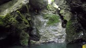 skalní útes : FPV, CLOSE UP: Happy active adventurous young guy on fun canyoneering experience in beautiful gorge in Slovenia, plunging off high steep rocky wall into refreshing river pool splashing waterdrops Dostupné videozáznamy
