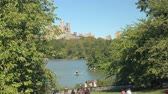 時代遅れの : NEW YORK, USA - SEPTEMBER 28: People in New York enjoying sunny spring day in lush green Central Park. New Yorkers and tourists sitting on benches and rowing boats on romantic lake in sunny Manhattan
