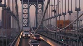 multilane : NEW YORK, USA - SEPTEMBER 23rd 2016: Vehicles caught in traffic jam driving over Manhattan bridge at beautiful misty pink dawn with downtown Manhattan business district skyscrapers in the background