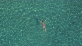 AERIAL: Attractive young Caucasian woman in bikini swimming under surface in beautiful turquoise ocean. Sun rays penetrating sparkling transparent water revealing stunning rocky and sandy sea bottom