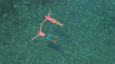 AERIAL, DISTANCING: Happy girlfriend and boyfriend holding hands, relaxing, laying and floating on water surface near amazing wild exotic beach in transparent turquoise crystal clear ocean lagoon