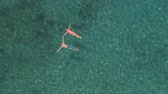 AERIAL, APPROACHING: Smiling girlfriend and boyfriend holding hands, floating on water, swimming starfish float in wild exotic lagoon. Transparent water revealing stones and stunning sandy ocean floor