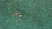 AERIAL: Girlfriend and boyfriend swimming in crystal clear ocean lagoon towards rocky shore on amazing hot and sunny day. Sun rays penetrating transparent water shining on beautiful sandy sea floor Stok Video