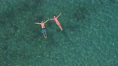 AERIAL, DISTANCING: Happy and loving girlfriend and boyfriend holding hands, relaxing and floating on water surface in amazing crystal clear ocean lagoon with visible rocks and stones on the seabed Stok Video