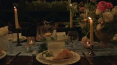 Slow panorama of festive  holiday table with nice serving, croissant, candles, macaroons, flowers (peonys, roses, lilys of the valley).