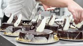 еда : Pastry chef decorating several cakes in the kitchen of the pastry shop.