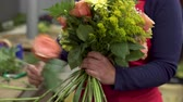 virágárus : Close up of female florist creating beautiful bouquet at flower shop.
