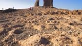 Roque Nublo mountain in Gran Canaria, Canary Islands on a blue sunny day. Cinematic camera movement.