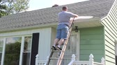 cephe : Guy Climbing the Ladder Putting Up Gutter Covers Stok Video