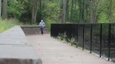 runners : Jogger in the Park on a Bridge Towards Camera