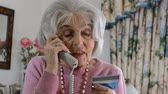 Confused senior woman giving out credit card details over the phone Stock mozgókép