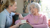 Young female carer talking to unhappy senior woman sitting in armchair