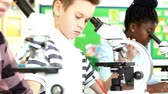 Line of three pupils in science class using microscopes and making notes on their findings