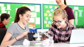 Two female pupils building model robotic car are joined by their female teacher who discusses the project with them