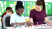 Girl with female tutor in science lesson using model to study molecular science Stock Footage