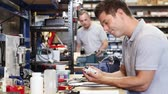 Engineer Helping Male Apprentice In Factory To Measure Component Using Micrometer