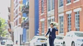 Businessman Using Mobile Phone Crossing City Street With Suitcase In Slow Motion Stock Footage