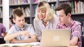 репетитор : Female Teacher Helping Two Male High School Students Working At Laptop In Library Стоковые видеозаписи