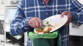 Man Scraping Food Leftovers Into Garbage Bin
