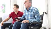 Mature Man In Wheelchair Sitting With Friend Watching Sports On Television
