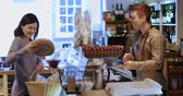 assistente : Female Customer Buying Loaf Of Bread From Male Sales Assistant In Delicatessen