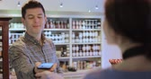Male Customer Making Contactless Payment For Shopping Using Mobile Phone In Delicatessen Stock Footage