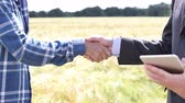 Close Up Of Businessman Shaking Hands With Farmer In Front Of Wheat Field Stock Footage