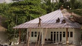 honey moon : Few asian people build hay roof of white modern bungalow on tropical island near the beach Stock Footage