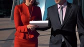 slomo : Slow motion. Young friendly smiling businessman sign his employee secretary in red suit documents on the run . Modern glass building dictrict at the background. Stock Footage