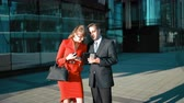 business : Young businessman make an offer with tablet PC to brown hair sexy attractive businesswoman in red dress. Handshake. Glossy district bg wide shot. Sunny day Stock Footage