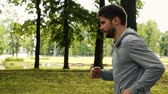 karşı : attractive powerful sportsmanman running in the park in gray jacket. Profile steadicam shot. Green trees background. Extreme slow motion footage.