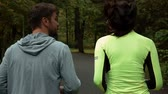 trotting : Tracking slow-motion of girl and guy communicating and smiling during morning jog. They running at the park and has a conversation on asphalt road. Stock Footage