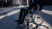 Slow motion shot of a businessman with in wheelchair walking and turning around and look at camera on the business district square. Happy smiling disabled man. Middle view