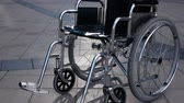 Disabled wheelchair rolling near modern business district. steadicam shot. Imminent illness concept. Disease. Slow motion, Stock Footage