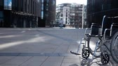 Cripple wheelchair rolling near modern building. Sunset or sunrise. Imminent illness concept.
