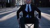 Young disabled cripple businessman in formal suit and tiemove in wheelchair on camera outdoor near business centre. look sad or have neutral emotion. Stock Footage